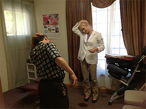 Hmong woman receiving chiropractic adjustment for whiplash injury